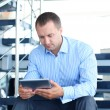 Businessman sitting on stairs with electronic tablet — Photo #41679749