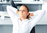 Portrait of smiling woman sitting and resting inside the office — Stock Photo