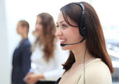 Young employee working with a headset and accompanied by her team — Stock Photo