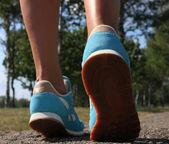 Vrouw schoenen uitgevoerd op het asfalt — Stockfoto