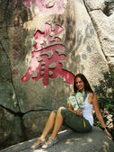 Young woman sitting on a stone with chinese fan, A-Ma temple, Macau — Stock Photo