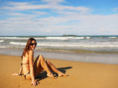 Junge frau sitzt an einem strand, playa el limon, dominikanische republ — Stockfoto