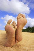 Sandy feet on a tropical beach — Stock Photo