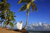 Ung kvinna i vit klänning på en strand — Stockfoto
