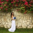 Young woman in wedding dress posing in front of the stone wall w — Stock Photo