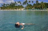 Young woman in bikini floating in clear water — Stock Photo