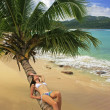 Young woman in bikini laying on leaning palm tree at Rincon beac — Stock Photo #25905203