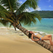 Young woman in bikini laying on leaning palm tree at Rincon beac — Stock Photo #25905209
