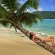 Young woman in bikini laying on leaning palm tree at Rincon beac — Stock Photo
