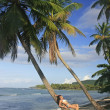 Stock Photo: Young woman in bikini laying on leaning palm tree, Las Galeras b