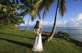 Ung kvinna i bröllopsklänning som står vid palm tree — Stockfoto
