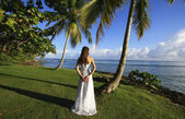 Young woman in wedding dress standing by palm tree — Stock Photo