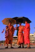 Monks with umbrellas walking near Mekong river, Vientiane, Laos — Stock Photo