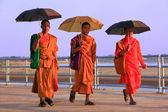 Monks with umbrellas walking near Mekong river, Vientiane, Laos — Stock Photo