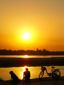 Silhouetted man with a dog watching sunset at Mekong river water — Stock Photo