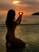 Young woman shaping heart with her hands at sunset, Langkawi isl — Stock Photo