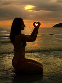 Young woman shaping heart with her hands at sunset, Langkawi isl — Stock fotografie