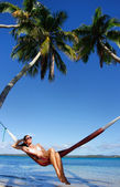 Young woman in bikini sitting in a hammock between palm trees, O — Stok fotoğraf