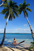 Young woman in bikini standing by the hammock between palm trees — ストック写真