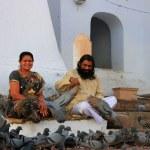 Indian man and woman feeding pigeons near holy lake, Pushkar, In — Stock Photo #45003683