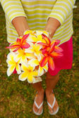 Young woman holding white and pink plumeria flowers in her hands — Stock Photo