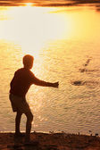 Silhouette of a boy throwing stones in a water, Khichan village, — Stockfoto