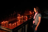 Tourist standing by the candles in Ostrog Monastery, Montenegro — Stock Photo