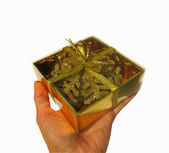 Gift golden color with a bow in hand isolated on white backgroun — Stock Photo