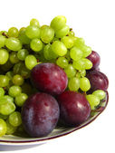 Green grapes and plums on a plate isolated on white background c — Stock Photo