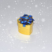 Golden Gift Box in the form of heart with a blue ribbon in snowf — Stock Photo