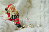 Santa Claus sitting on white fur with pearls — Stockfoto