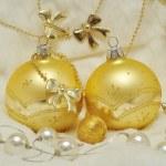 Christmas decoration - golden balls on white fur, bows, pearls — Stock Photo
