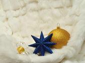 Juldekorationer - star, bollar och pärlor på vit päls — Stockfoto