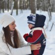 Stock Photo: Young mother and child talking on winter walk in park