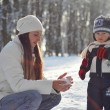Young mother making snowballs for a kid on a winter walk in the — Stock Photo