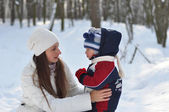 Young mother and child talking on a winter walk in the park — Stock Photo