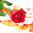 Romantic scenery - red rose on orange petals with hearts and pea — Stock Photo