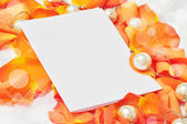 Sheet of white paper on orange petals of roses and pearls — Stock Photo