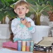 Stock Photo: Cheerful kid playing with paint preparing to draw