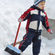 Stock Photo: A child with a brush running on snowy landscapes with space for