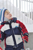 Cheerful boy in snowy landscapes looking up with space for text — Stock Photo