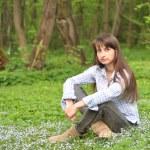 güzel bir genç kadın parkta çim üzerinde oturur. — Stok fotoğraf