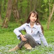 Beautiful smiling young woman sitting on the grass in the park — Stock Photo