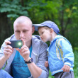 Stock Photo: Dad photographing by phone and toddler enthusiastically observin