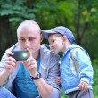 Dad photographing by phone and toddler enthusiastically observin - Stock Photo