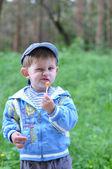El niño come dulces en un palo con una mirada descontento en la fac — Foto de Stock