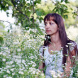 Beautiful romantic girl in a field of daisies on blurred backgro — Stock Photo