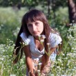 Stock Photo: Beautiful Slavonic Girl standing in a field of daisies on blurre
