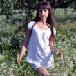 Stock Photo: Beautiful Slavonic Girl standing in a garden on blurred backgrou