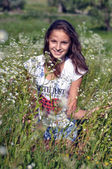 Beautiful girl smile and relaxing in a field of daisies — Stock Photo